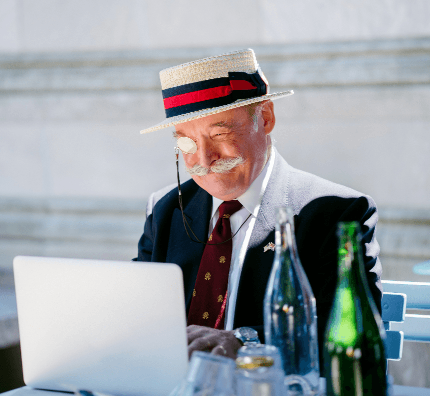 Elderly gentleman sitting in front of a laptop with wine bottles on the table