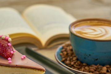 Image of a cup of coffee with a piece of cheesecake and a book in the background