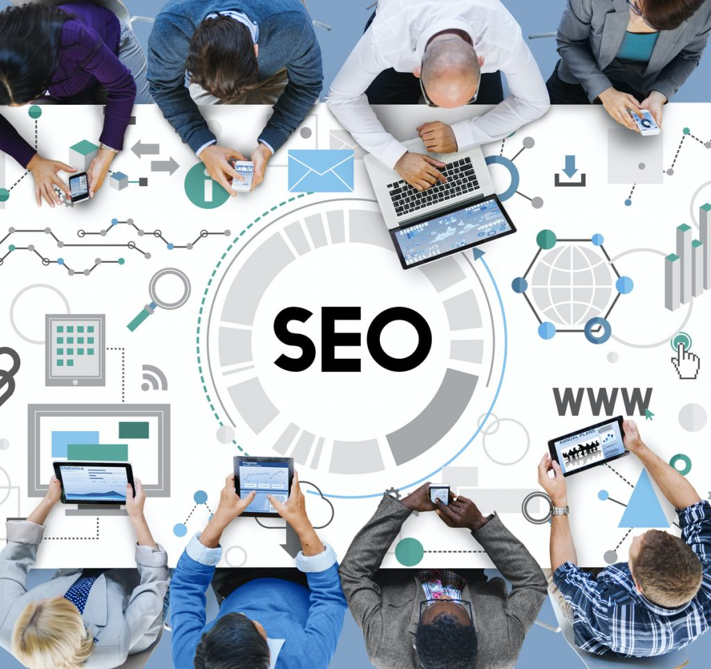 People sitting around a desk with their phone in their hands. View from the top and SEO process depicted on the table